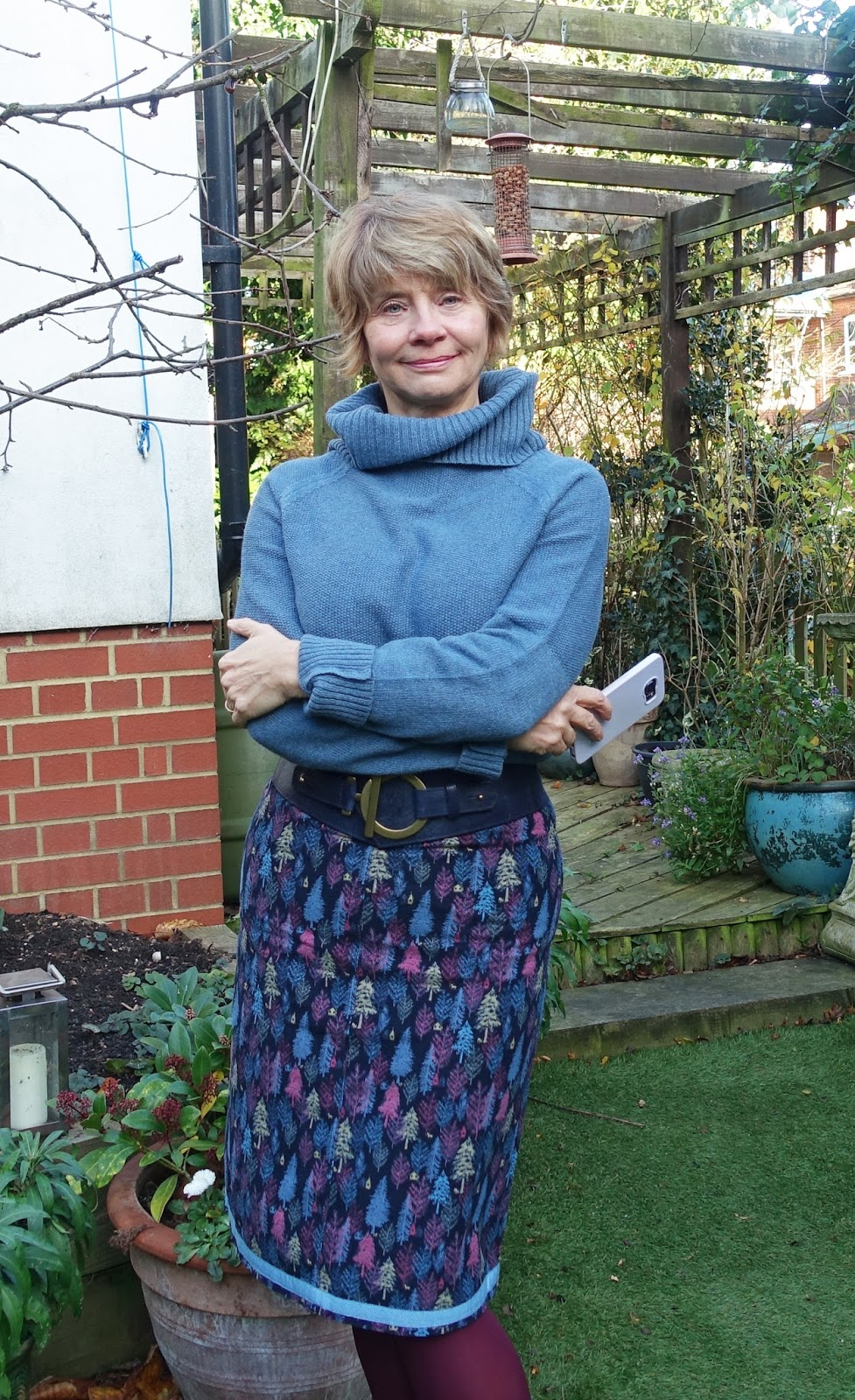 Image showing an over 50s woman in a knee length skirt with tree print and jumper and tights in blue and mauve shades.