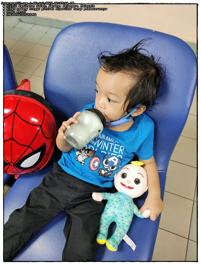 Picture of Aidan drinking milk while waiting for his turn for a health check -up at the Salak Health Clinic with his friend the baby Cocomelon and a Spiderman bag.