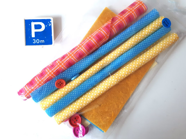 Package of rolled fabric pieces with coordinating felt pieces and buttons. On the pack is a price tag that says 'Vinnies $4'