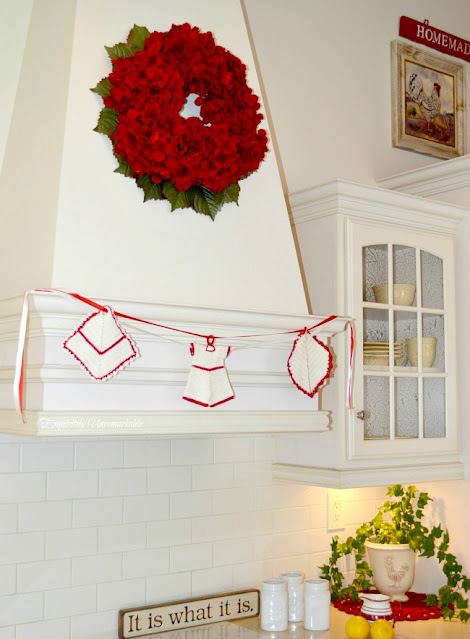 Kitchen range hood with red wreath and crochet pot holder banner