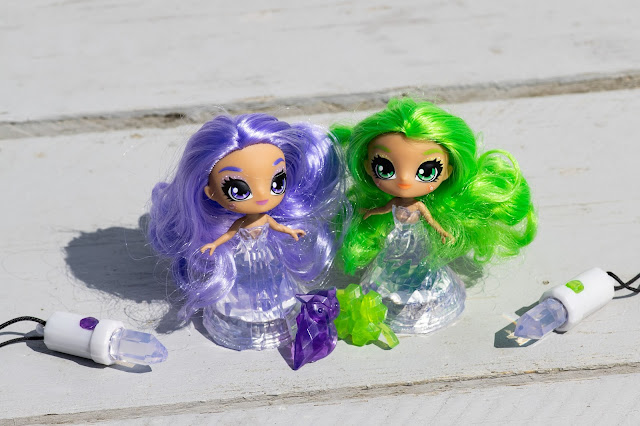 A display of 2 Crystalina dolls, their amulets and hair clips
