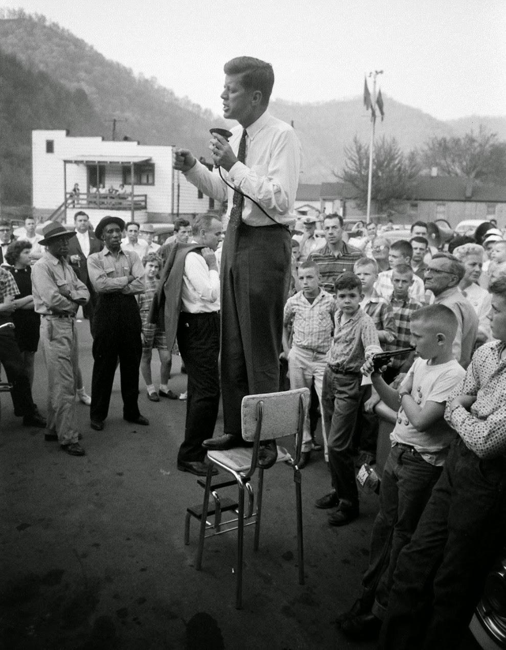 John F. Kennedy hace campaña en la zona rural de Virginia Occidental buscando apoyo para la primaria del 10 de mayo, precariamente encaramado en una silla alta para pronunciar su discurso, 1960.