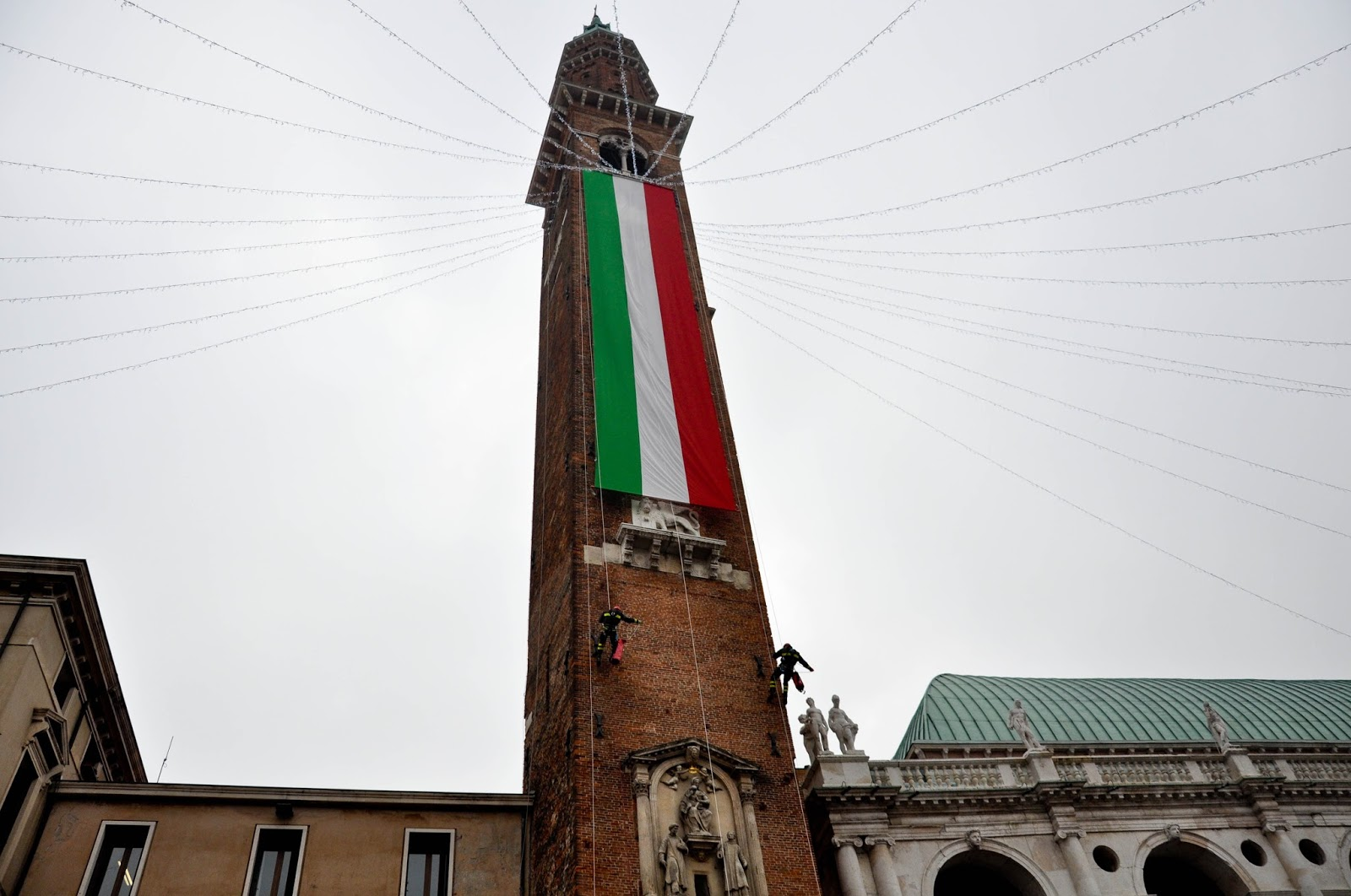 Firefighters climbing down the clock tower of the Palladio's Basilica, Saint Barbara celebration, Vicenza, Veneto, Italy