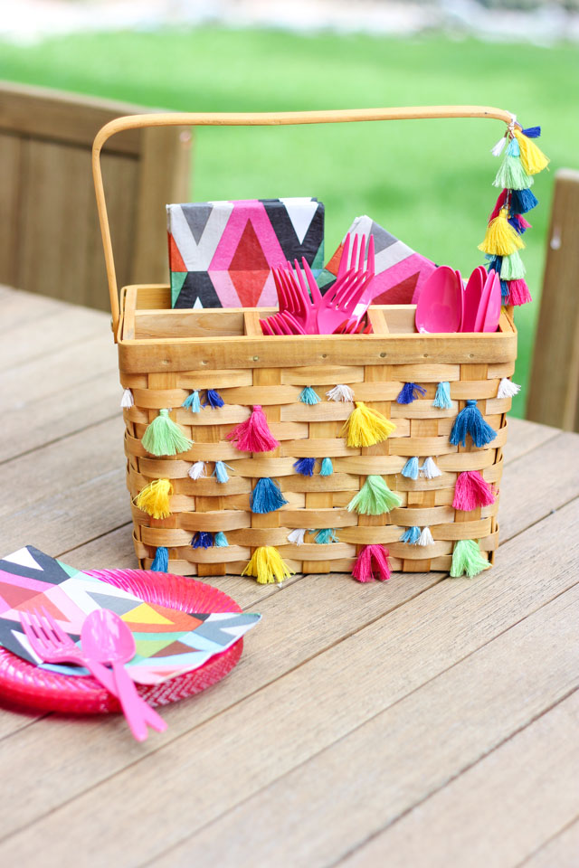 Decorate a basic picnic utensil basket with tassels for boho chic summer entertaining!
