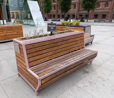Bench with a social distancing sign in Spinningfields, Manchester.