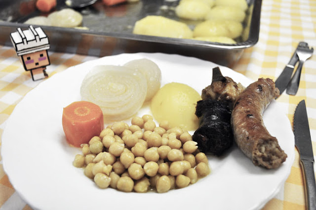 el muñeco que representa el logo del blog junto a un plato de garbanzos
