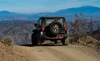 Black color jeep, parked jeep on a gravel road, rear view of a jeep