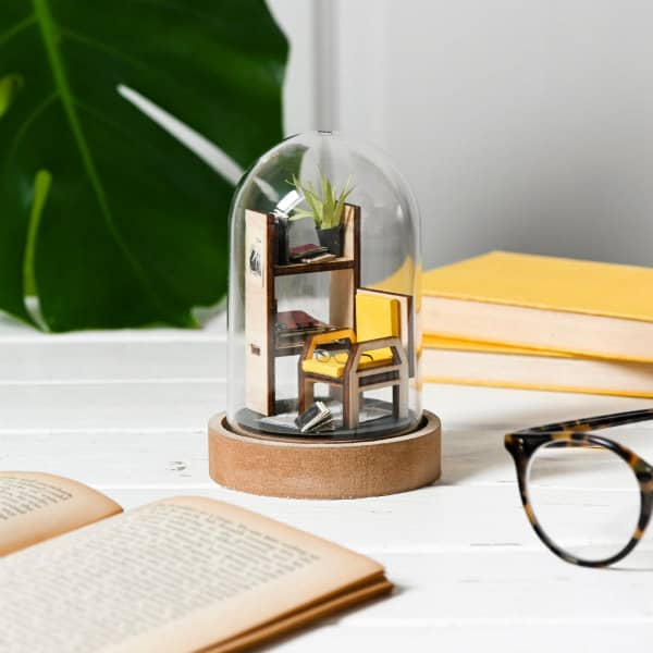 library scene including book shelf, books, and chair inside domed glass jar with wood base