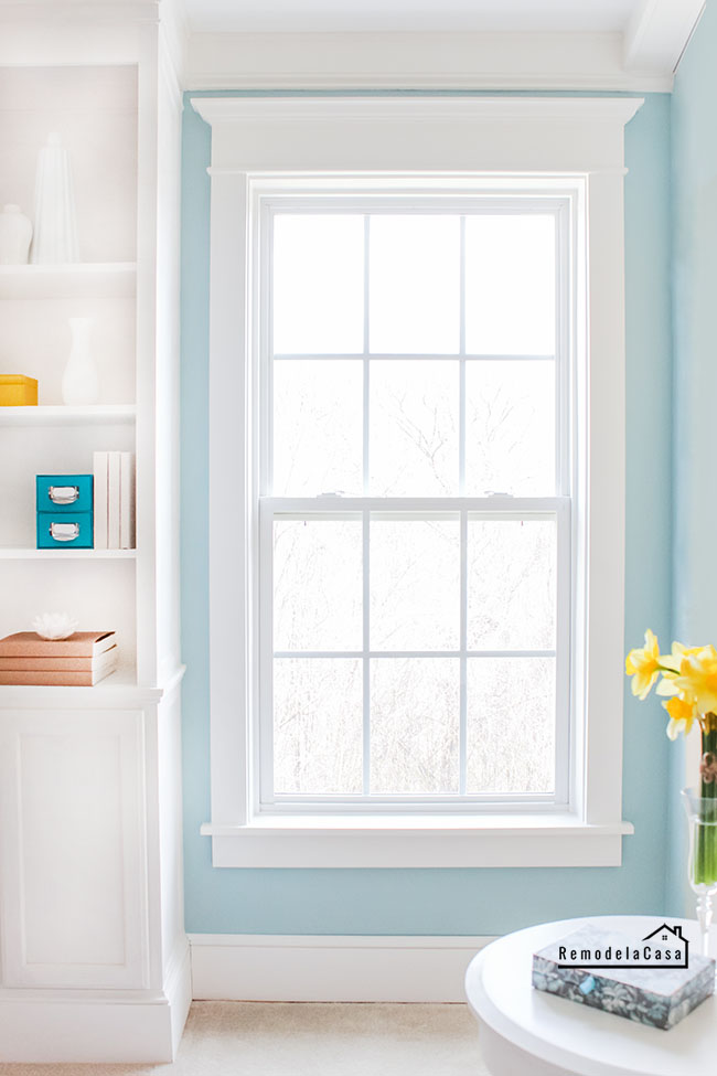 Window in bedroom with built-in and teal color wall