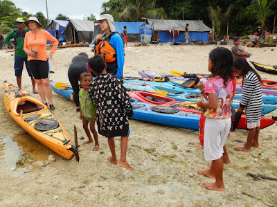 Nigel Foster photo, fishing camp on beach with tarp shelters and curious children