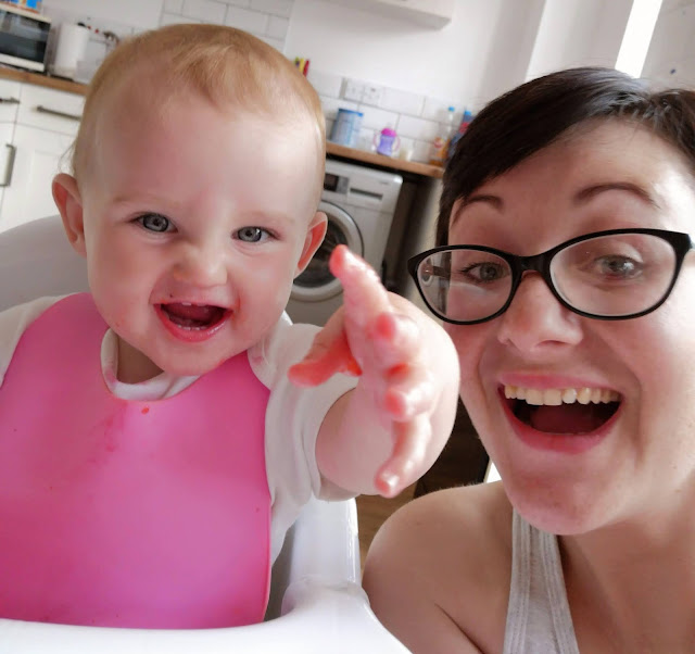 Image of baby and mummy sat at the dining table. Baby is wearing plastic catch all bib. Both are smiling and laughing.