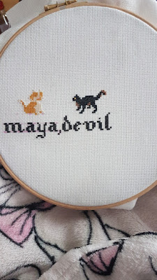 cross stitch embroidery of a red and a black cat with the text maja and devil