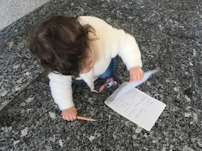 Kleinkind mit Stift und Schreibblock in der Hand