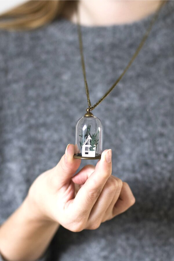 clear dome necklace filled with paper cut greenery growing from tiny white greenhouse