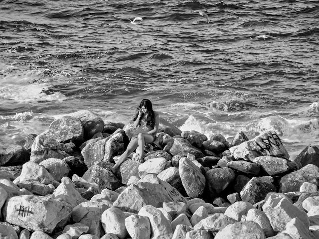 B&N.Mujer hablando por celular desde las rocas costa del mar.