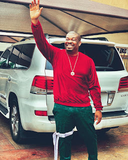 Don jazzy wears a band tie on his right leg, while raising hands up