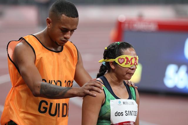 Guia atras de atleta cega com uniformes prestes a correr