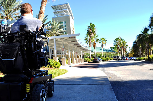 A man in a power wheelchair rolls toward a tall building. Around the building, there are a number of palm trees. The sky is a clear, bright blue.