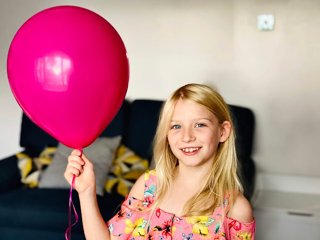 An 8 year old girl with long hair holding a big pink balloon