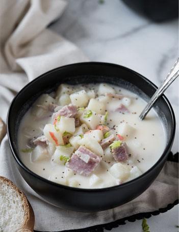 Black bowl of potato soup