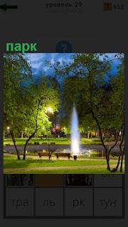 в парке в середине работает фонтан, стоят скамейки