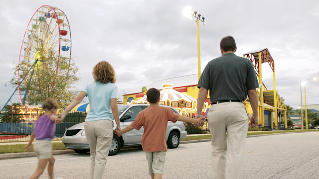 a family of four walking toward the front entrance of an amusement park