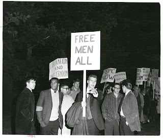 "Image of dartmouth students protesting George Wallace's speech outside of Webster Hall. A student in the foreground holds a sign that reads ""Free Men All."""