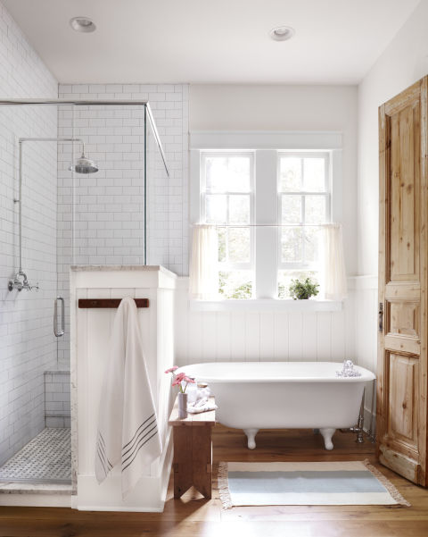 Beautiful modern farmhouse style bathroom with vintage clawfoot tub, knotty pine door and inspiration on Hello Lovely Studio