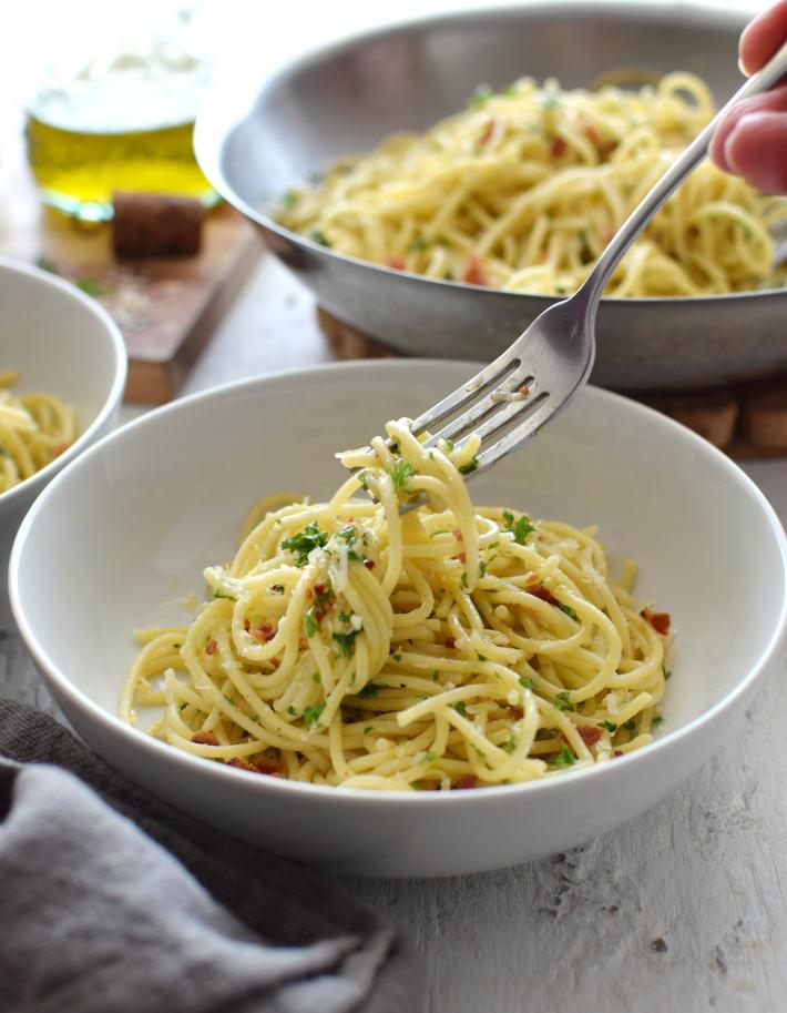Pasta sencilla con ajo, perejil y queso parmesano, servida en un plato, lista para consumir