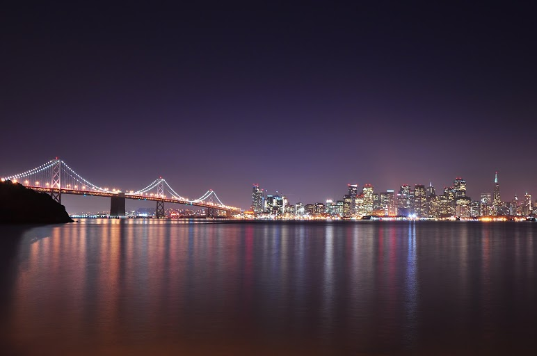 Lighted High Rise City Buildings Across Body of Water during Nighttime