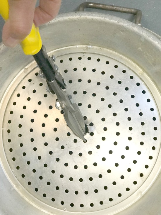 Using tin snips to cut an aluminum colander to make a light