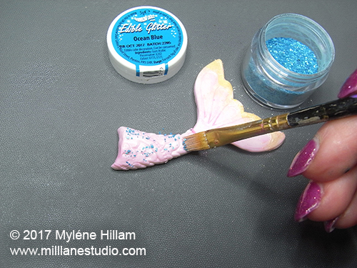 Adding blue sugar crystals to the scales of the mermaid's tail.