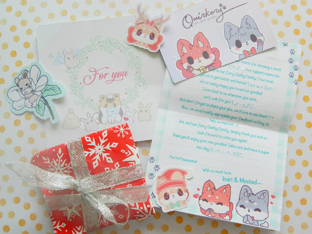 A photo showing a christmas gift from Quirkory, wrapped in red paper with a silver ribbon, a letter, stickers of eevee, a pokemon, and fox mascots