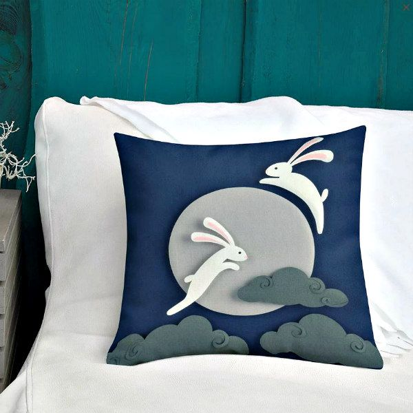 pillow printed with image of two paper sculpture white rabbits jumping over moon with clouds below them