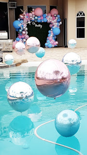 Swimming pool decoration with floating helium balloons and balloon arch with greenery backdrop