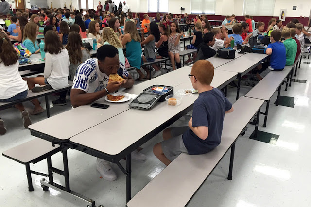 Florida State University wide receiver Travis Rudolph eats lunch with an autistic student while visiting a Tallahassee middle school