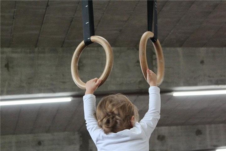 小さな子供がジムナスティックスで運動している写真