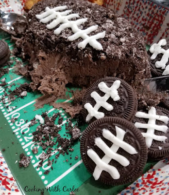 inside of chocolaty cookies and cream cheese ball with Oreos with football lace frosting in foreground