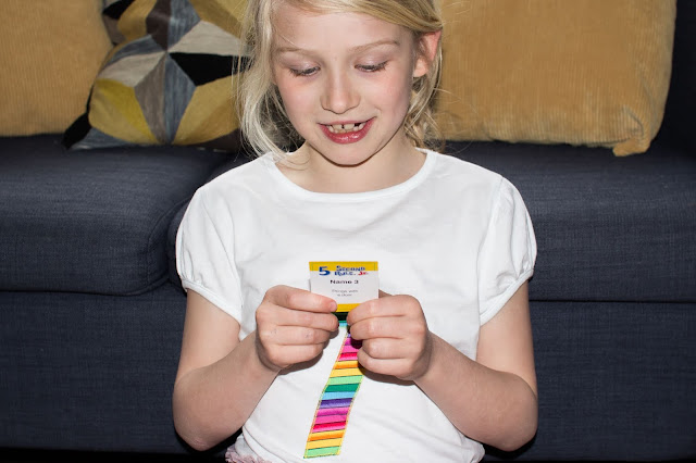 A girl reading a question card from 5 second rule jr.
