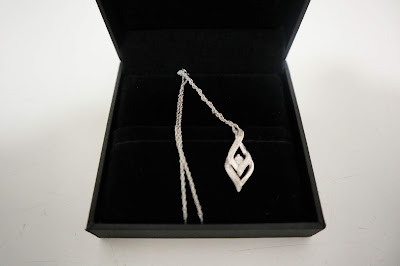 A diamond teardrop style necklace on a silver chain in a black gift box.