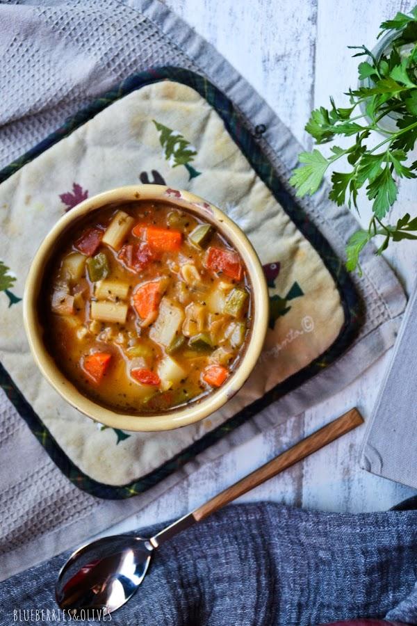 Olla cerámica roja llena con hoja laurel, bol cerámica con sopa, paño lino gris, libro cocina del mundo, cuchara mango madera,hojas perejil fresco