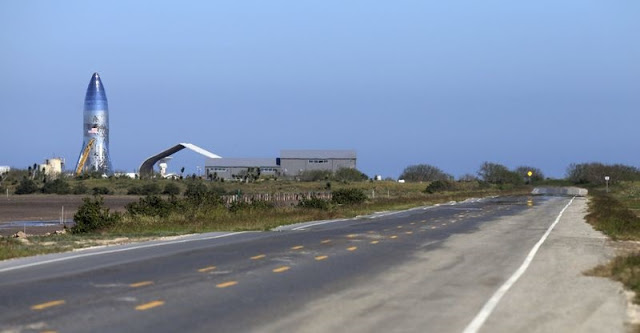 A SpaceX prototype Starship hopper, left, rises at Boca Chica Beach, Texas, on Jan. 12 along Texas Highway 4. (Miguel Roberts / Associated Press)