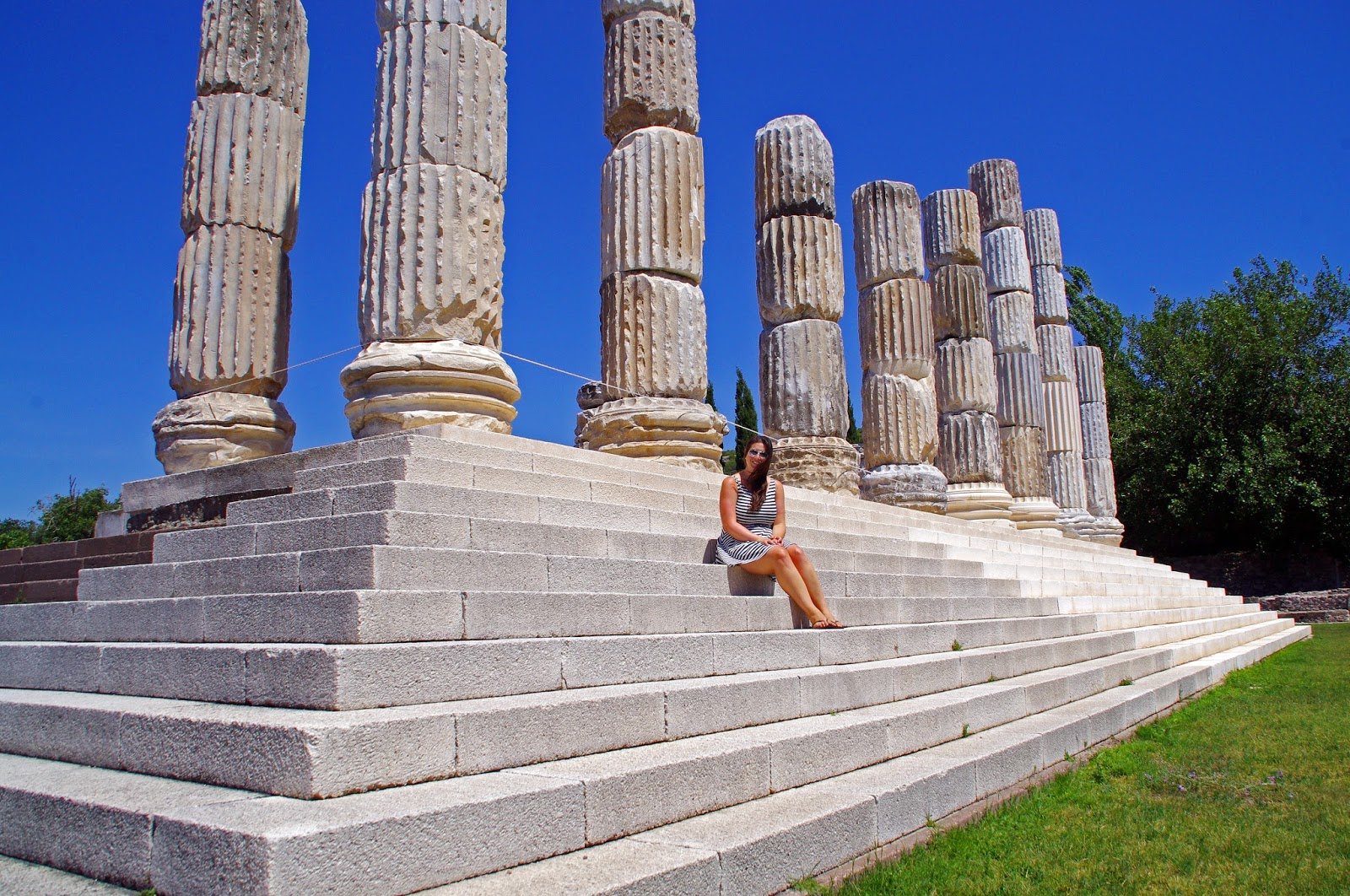 Simone sitting on steps of Apollon Symintheion ruins