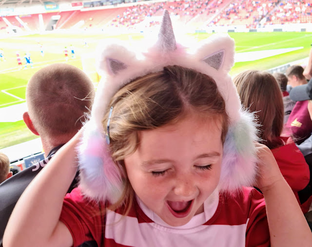 Image of a pre school girl/ toddler pulling an excited face whilst wearing fluffy unicorn ear muffs and placing her hands over her ears. Behind the girl is The Keepmoat Stadium where a match is in play. The girl is wearing a red and white striped Doncaster Rovers children's football shirt.