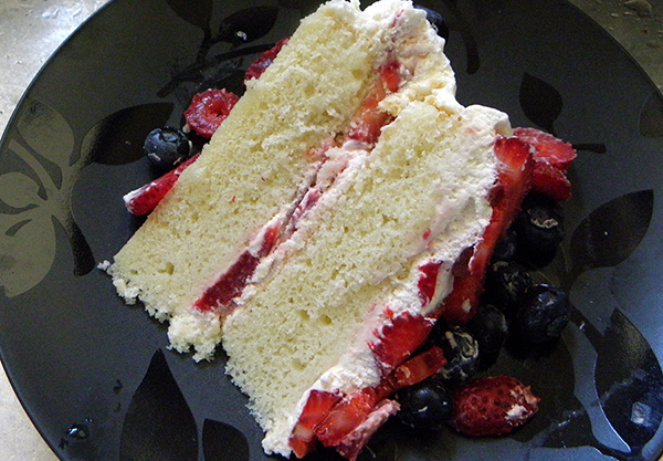 Slice of Berry Whipped Cream Cake on Plate