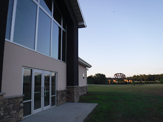 the front of the Interpretive Center at Siouxland Freedom Park is seen from an angle, with the railroad bridge over the Missouri River visible in the background