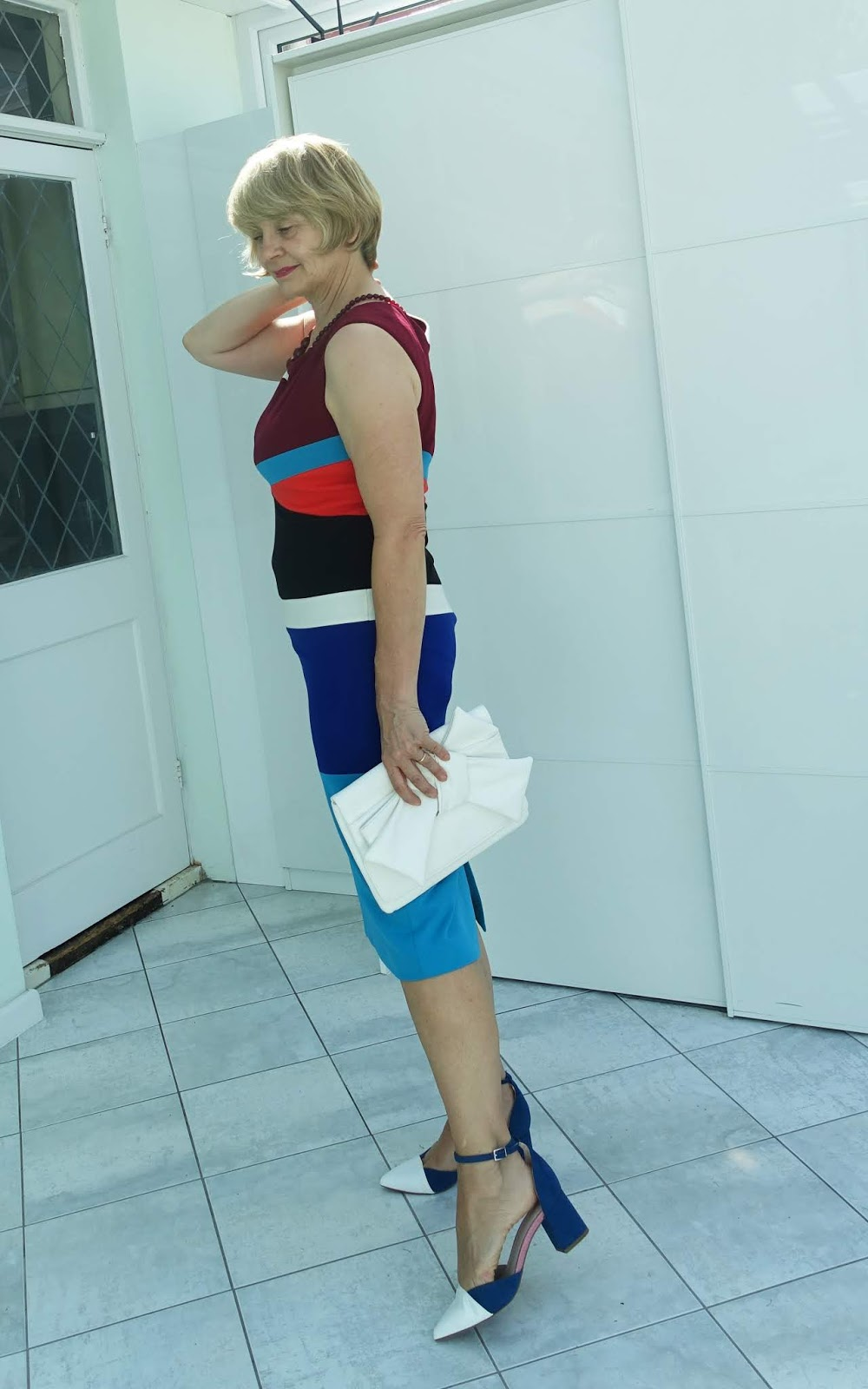 A colour block dress featuring teal, turquoise and burgundy from Anthropologie, worn with teal and white shoes and accessorized with a white clutch bag and burgundy necklace.