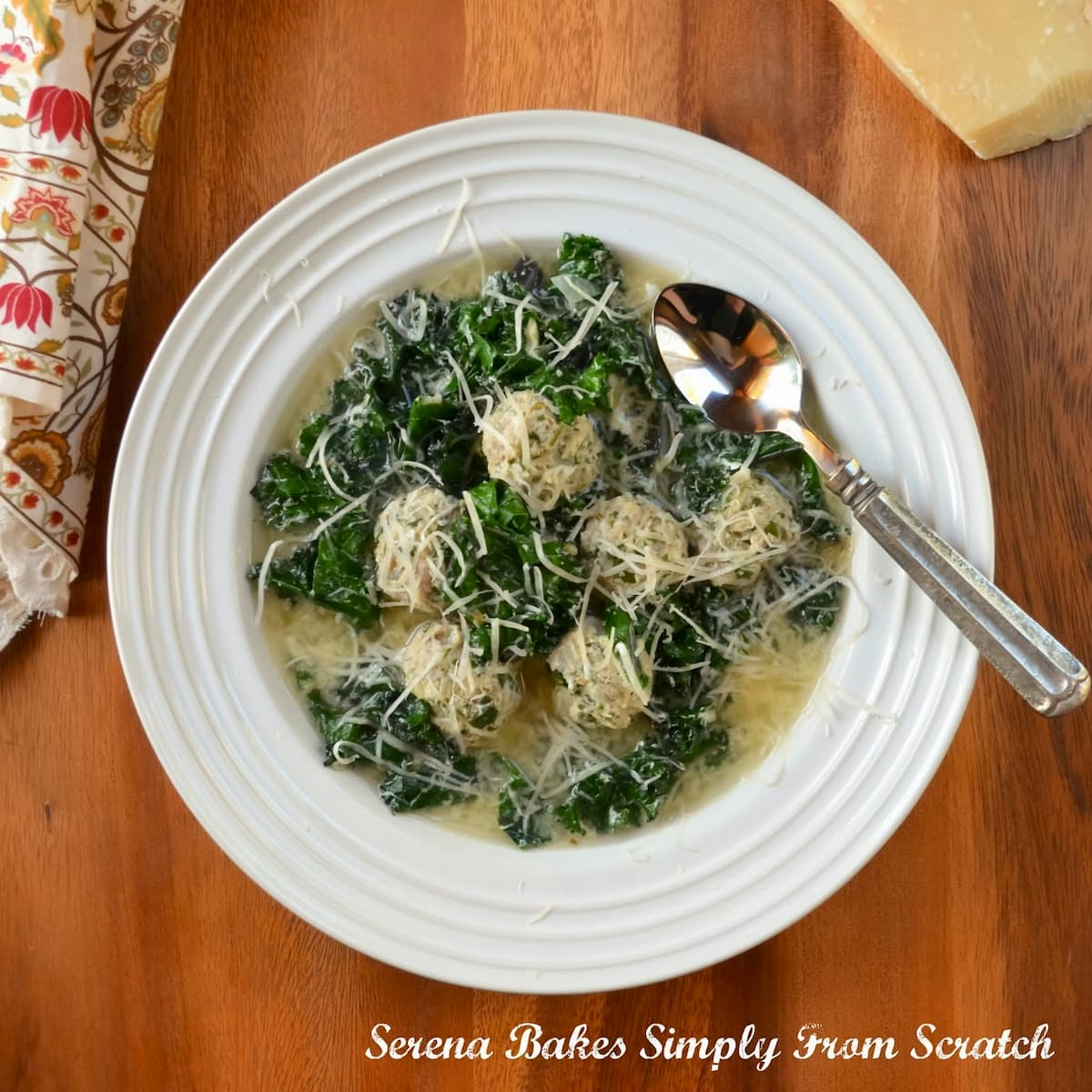 A bowl of Italian Wedding Soup with Meatballs, kale and star pasta with fresh parmesan cheese over the top.