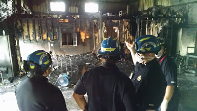 Three investigators survey the aftermath of a fire.