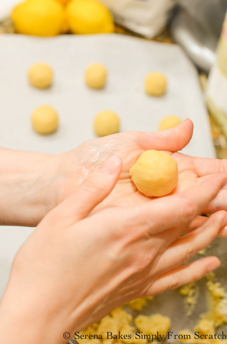 Lemon Snowball Cookie Dough being rolled into balls.